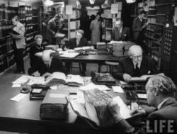 Mensen doen onderzoek in Stockholms Stadsarchief. In kelder burgerbescherming Fotograaf: Carl Mydans, 1955