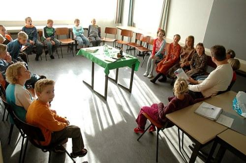 Kindernevendienst. De kinderen zitten in de kring en de leiding leest voor.