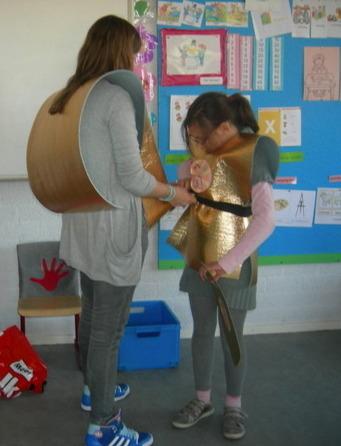 Twee kinderen helpen elkaar met het harnas. Straks zijn ze soldaten van Saul.