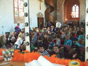 Blik in de kerkzaal. Daar zitten kinderen uit groep 5 tot en met 8 van 2 basisscholen. Fotograaf: Peter Verhage