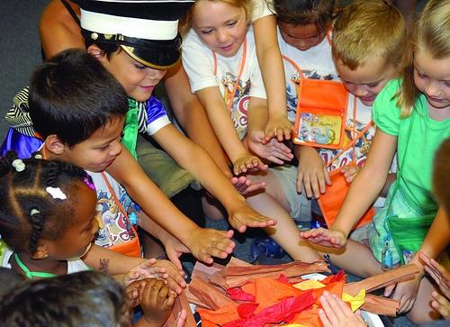 Kinderen zitten rond een vuurtje van crèpepapier