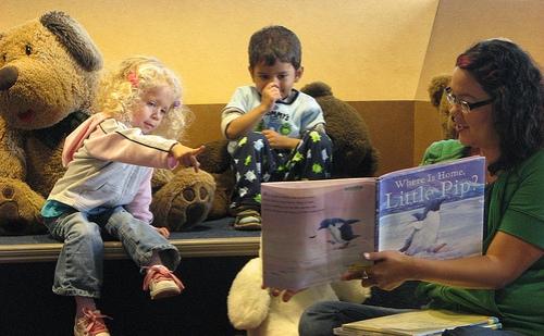 Een vrijwilligster leest voor in een bibliotheek