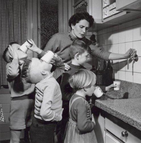 Drinken. Vier kinderen in een Bruynzeel keuken (met granieten aanrecht) krijgen een beker water ( geen limonade!!). Moeder bedient de koud water kraan. Foto 1956.