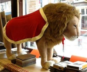 Koning Leeuw draagt een hermelijnen koningsmantel om.