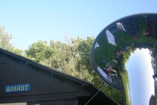 In het zicht van de bas is een stukje van het boshutterrein te zien