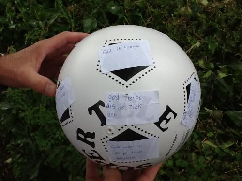 Voetbal met stikkers erop. Op één van de stickers is geschreven: God helpt als je ziek bent