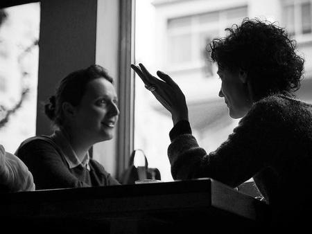 Twee vrouwen zijn in gesprek met elkaar. Ze kijken elkaar aan.
