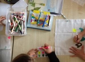 Bovenaanzicht van kind dat kaart kleurt, op zakdoek tekent.