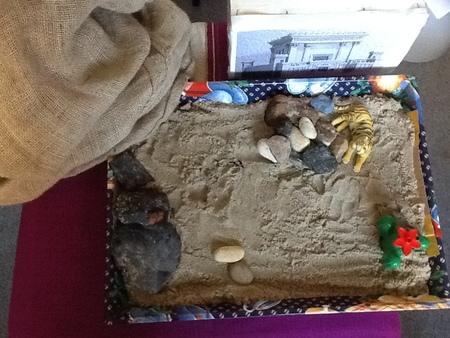 Bak met zand, stenen, een liggende tijger, cactus stellen een woestijnlandschap voor. Er is ook een tempel zichtbaar en jute zak die een berg moet voorstellen.