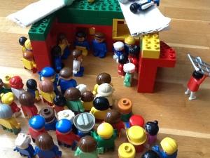 Veel poppetjes staan voor een huis. Het dak is open en er liggen mannetjes op. Een poppetje loopt weg en draagt een bed.