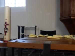 liturgietafel in een kerk. Er liggen gele memoblaadjes op.