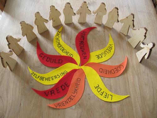 Op 9 vliten vlammen zijn de namen van de vruchten van de Geest geschreven. 12 houten mensfiguren staan erom heen.