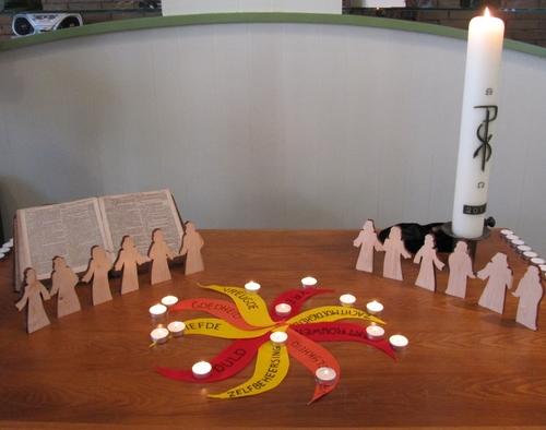 Liturgietafel met 12 houten mensfiguren rond een waaier van vilten vlammen. Daartussen staan waxinelichtjes.