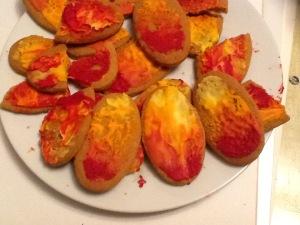 Bord met koekjes. Op de koekjes een rood, oranje, gele topping. Zo lijken het vlammen.