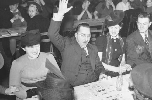Mensen zitten aan een tafel. Een man steekt zijn hand omhoog. Hij heeft bingo.