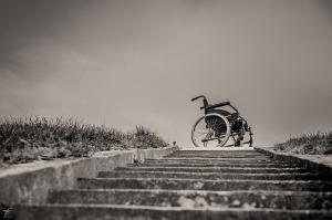 Foto van een trap van onderaf genomen. Bovenaan staat een rolstoel.