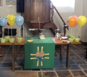 Liturgietafel met op 9 ballonnen staan de vruchten van de Geest
