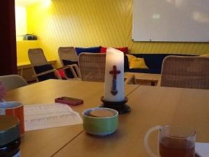 een tafel die gereed is voor de vergadering: mobieltje, papieren, kop thee, koekjes en een brandende kaars