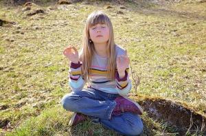 meisje zit buiten op de grond te mediteren