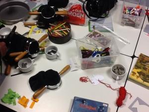 Tafel met rommel: collectezakken, snoep, kinderbijbel, scharen, potloden: restanten van een kindernevendienst