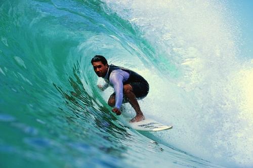 Man surft terwijl de golg bijna over hem heen slaat.