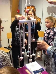 kinderen kindernevendienst hangen kralen aan een krans