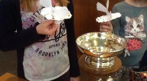 kinderen houden papieren duiven vast bij een doopvont
