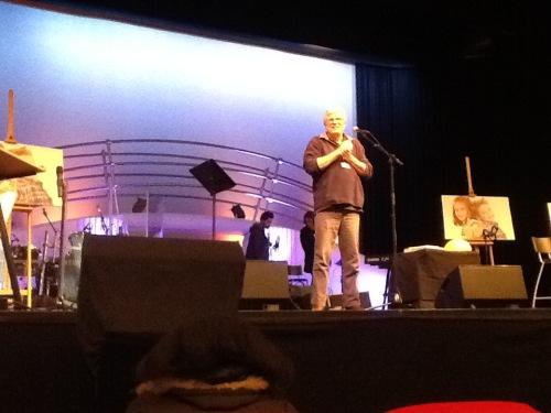 Bob Hartman spreekt tijdens RondomHetKind 2016. Een interessant congres voor mensen die kindernevendienst geven. Hij staat op het podium en kijkt de zaal in.