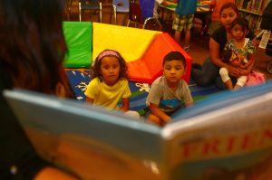 Over de randen van een boek zie je luisterende kinderen.