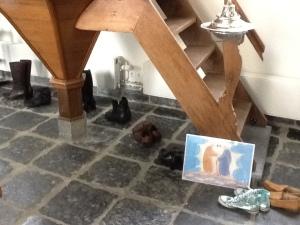 Onder een trap staan schoenen op een rij. Er is ook een doopvont zichtbaar en een afbeelding uit het 40dagentijdproject: stap voor stap