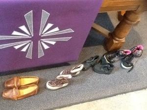 voor de liturgietafel staan schoenen op een rij. de kleur van het kleed is paars: lijdenstijd. Zo willen we het kindernevendienstproject verbeelden: stap voor stap