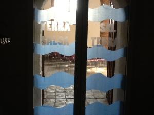 Op glazen kerkdeuren zijn blauwe golven water geplakt.
