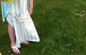 kind staat met een keukenschort aan in het gras
