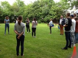 mensen staan in een kring op een grasveld