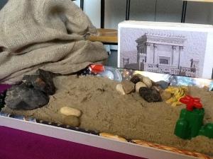 tafereel met zand, stenen en tempel dat de verzoeking in de woestijn moet verbeelden