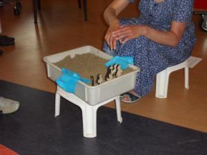 bak met zand waarmee het Exodusverhaal verteld is en vertelster op een krukje: bijbelverhaal verteld geïnspireerd op godly play methode