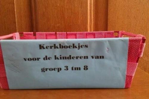 kerkboekjes voor de kinderen van groep 3 t/m 8, die tekst is bevestigd aan de zijkant van een plastic mandje