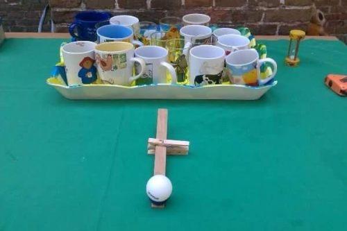 Wip met pingpongballetje ligt voor een dienblad met kindermokken en glazen