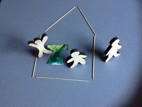 Huis van sateprikkers, 3 houten poppetjes en papier in de vorm van een jas