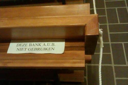 De kerkbank is afgesloten met een touw. Er ligt een briefje: deze bank alstublieft niet gebruiken.