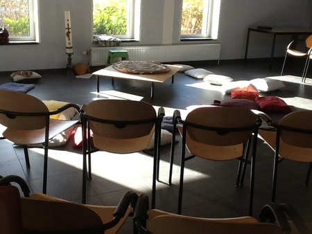 lage tafel met woestijnzak, kussens en stoelen staan er in een halve kring omheen. Er is ook een paaskaars.