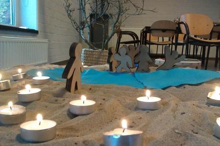 waxinelichtjes in het zand met godly play poppetjes op de achtergrond