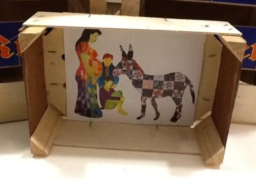mandarijnenkistje staat op de zijkant waardoor de bodem een ingelijst schilderij lijst met afbeelding maria en de ezel