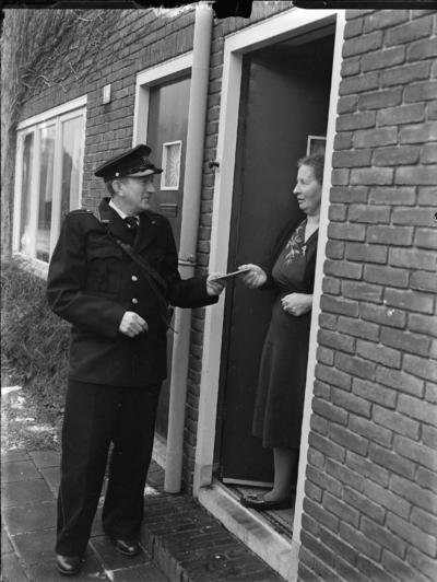 postbode geeft brief aan vrouw die in deurgat staat
