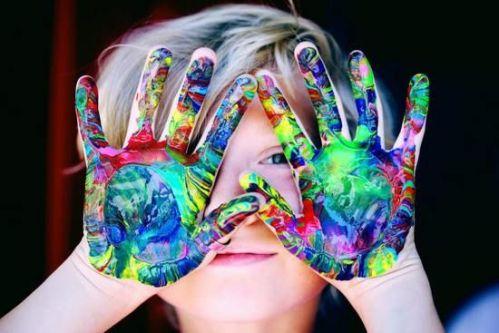 Een kind houdt handen voor het gezicht. handen zitten onder de verf