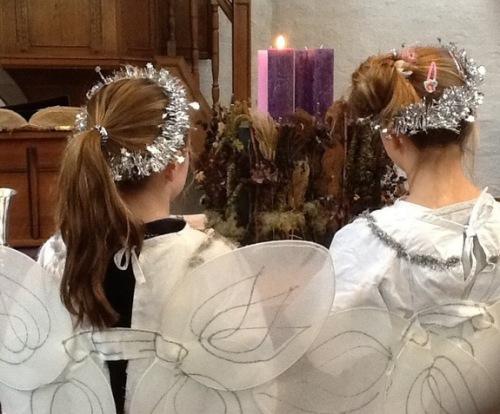 Twee kinderen op de rug gezien. Ze zijn verkleed als engel en hebben vleugels op de rug. Er brandt één adventskaars