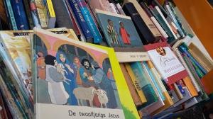 Boekje de Twaalfjarige Jezus ligt op een rij boeken op een rommelmarkt