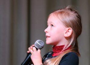 meisje houdt een microfoon vast en praat er door