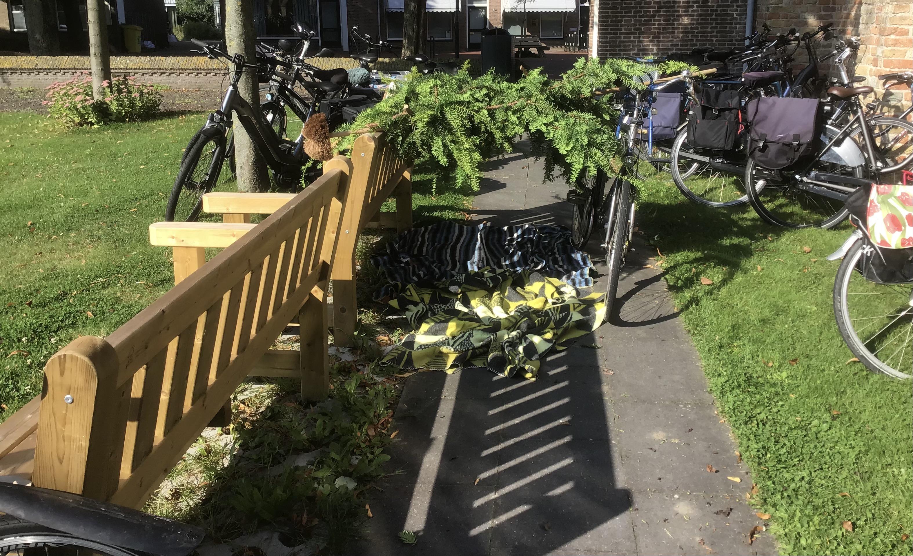 Tussen een bank en fiets liggen takken op een bezem en ragebol
